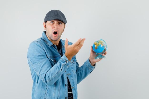 Jonge man met globe terwijl hij naar camera in jasje, pet kijkt en verbaasd kijkt