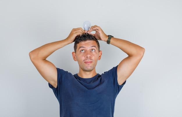 Jonge man met gloeilamp op zijn hoofd in donkerblauw t-shirt en op zoek grappig, vooraanzicht.