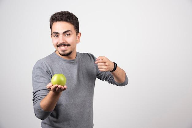 Jonge man met groene appel op grijs.