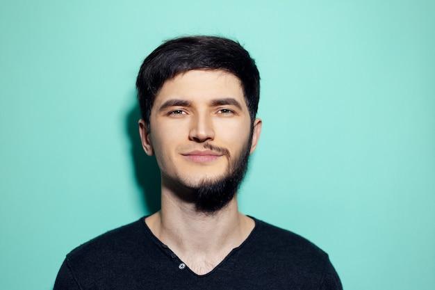 Jonge man met half geschoren gezicht op muur van aqua menthe kleur.
