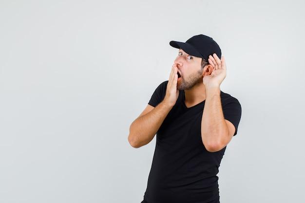 Jonge man met hand achter oor in zwart t-shirt