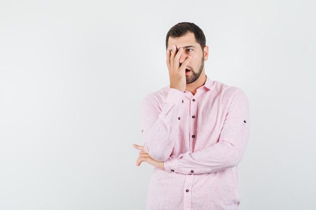 Jonge man met hand op gezicht in roze shirt en sorry op zoek
