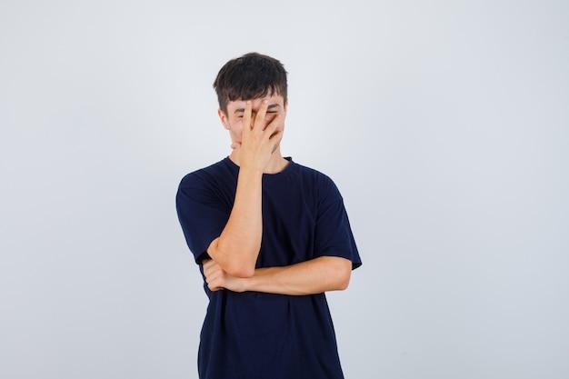 Jonge man met hand op gezicht in zwart t-shirt en op zoek opgewonden. vooraanzicht.