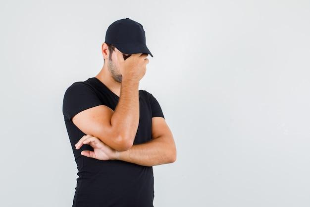 Jonge man met hand op gezicht in zwart t-shirt