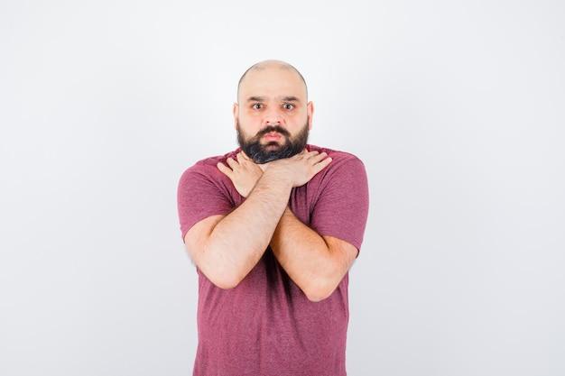 Jonge man met hand op keel in roze t-shirt vooraanzicht.