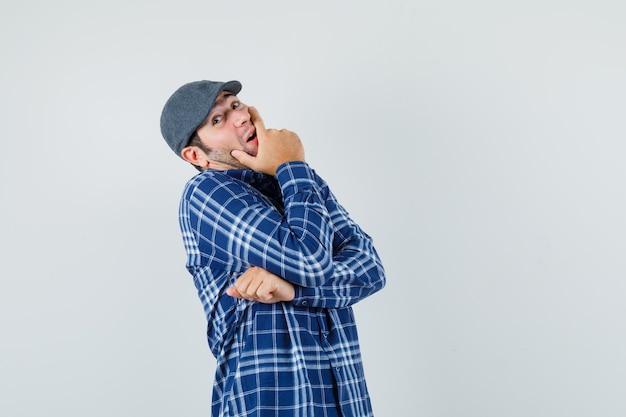 Jonge man met hand op mond in shirt, pet en op zoek naar optimistisch. vooraanzicht.
