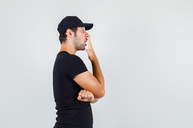Jonge man met hand op mond in zwart t-shirt