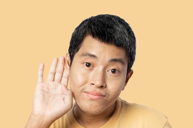 Jonge man met hand over oor luisteren en horen van geruchten of roddels. geheim concept