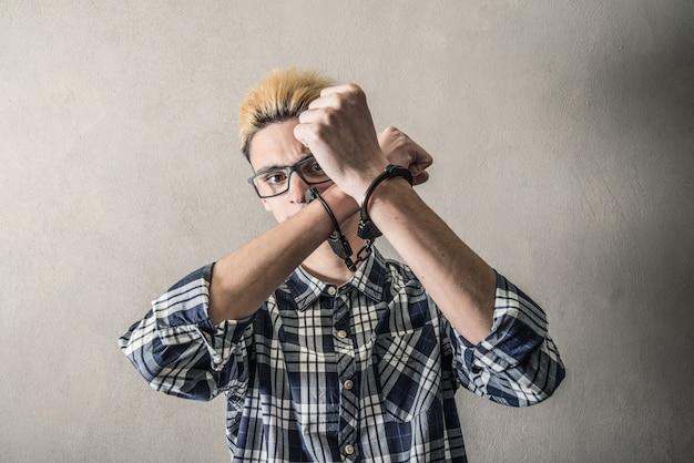 Jonge man met handboeien om de polsen