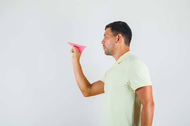 Jonge man met handgeschept papier vliegtuig in t-shirt.