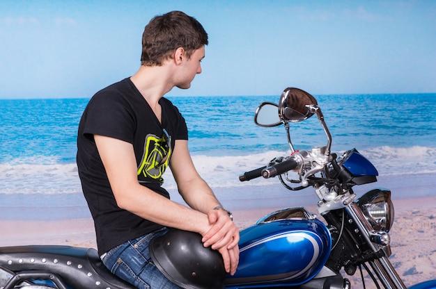 Jonge man met helm zittend op klassieke blauwe motorfiets en kijkend naar water op strand