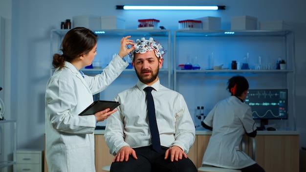 Jonge man met hersengolf scanning headset bespreken met neurologische onderzoeker over symptomen van ziekte. medisch wetenschapper die informatie over hersenscan schrijft op tablet die in laboratorium werkt