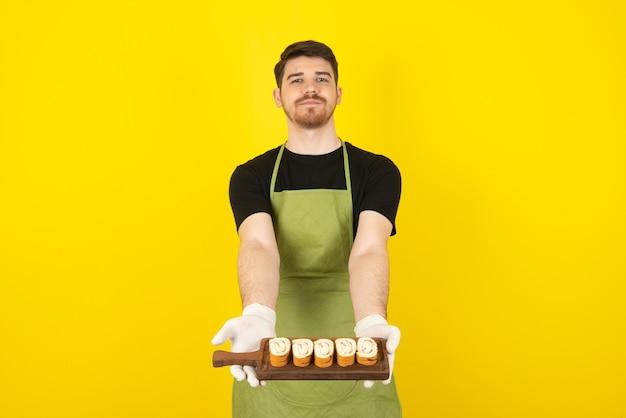 Jonge man met houten dienblad vol met plakjes cake op geel.