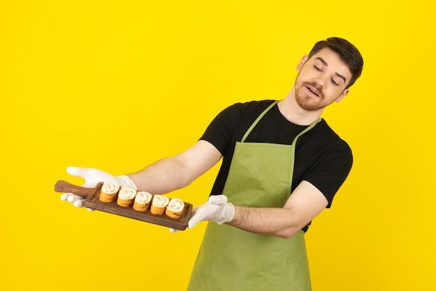 Jonge man met houten dienblad vol met plakjes cake.