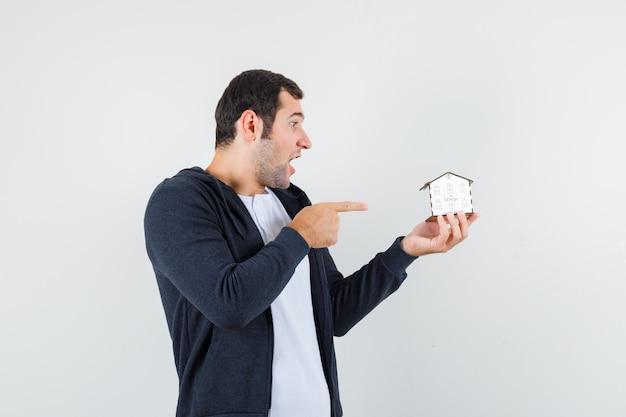 Jonge man met huismodel en wijst ernaar met wijsvinger in wit t-shirt en zwarte hoodie met rits aan de voorkant en kijkt verrast, vooraanzicht.