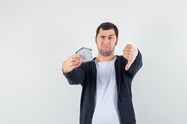 Jonge man met huismodel in de ene hand en duim omlaag in wit t-shirt en zwarte hoodie met rits aan de voorkant en ontevreden kijken. vooraanzicht.