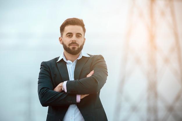 Jonge man, met jas en overhemd, ziet eruit als een ondernemer, met een ernstige uitdrukking, armen over elkaar. op een hemel en hoogspanning torens achtergrond. werk en jonge ondernemers concept