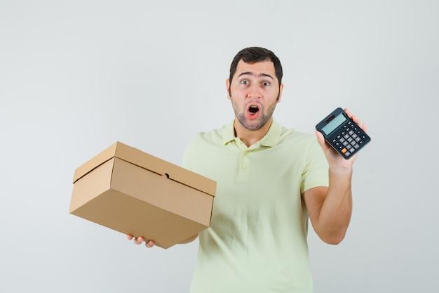 Jonge man met kartonnen doos en rekenmachine in t-shirt en op zoek verbaasd. vooraanzicht.