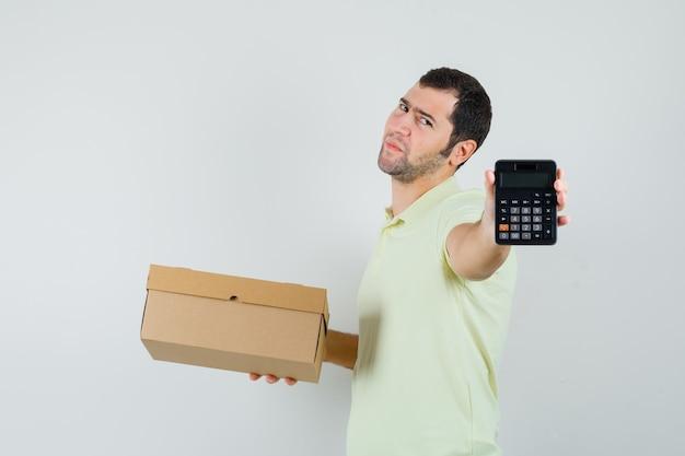 Jonge man met kartonnen doos en rekenmachine in t-shirt, vooraanzicht.