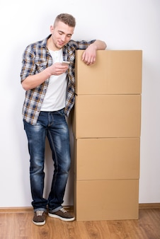 Jonge man met kartonnen dozen en mobiele telefoon.