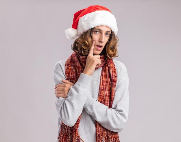 Jonge man met kerst kerstmuts met warme sjaal om zijn nek kijken met peinzende uitdrukking denken
