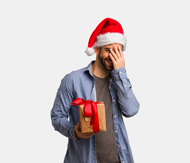 Jonge man met kerstmuts beschaamd en lachen op hetzelfde moment