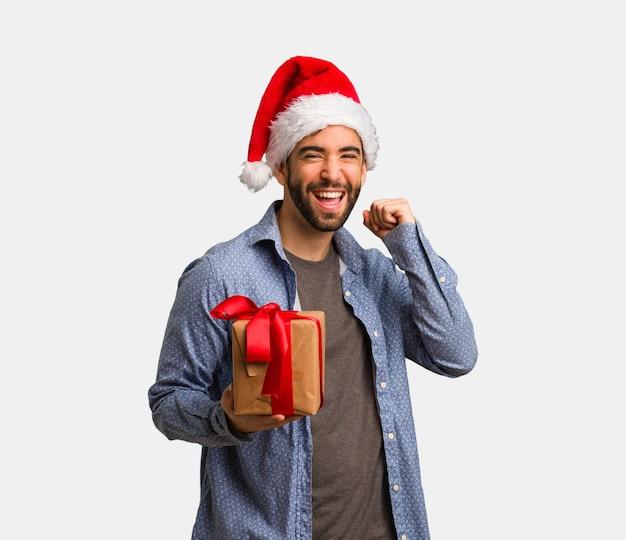 Jonge man met kerstmuts dansen en plezier hebben