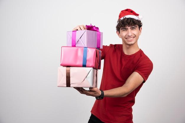 Jonge man met kerstmuts die zich gelukkig voelt en geschenken vasthoudt.