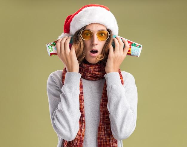 Jonge man met kerstmuts en gele bril met warme sjaal om zijn nek met kleurrijke papieren bekers over zijn oren en kijkt verrast over groene muur