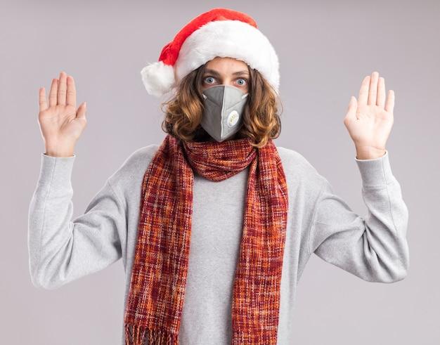 Jonge man met kerstmuts en gezichtsbeschermend masker met warme sjaal om zijn nek, bezorgd handen opstekend in overgave staande over witte muur