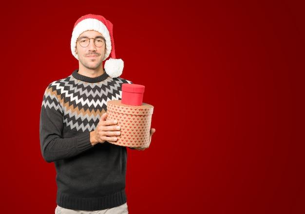 Jonge man met kerstmuts gebaren