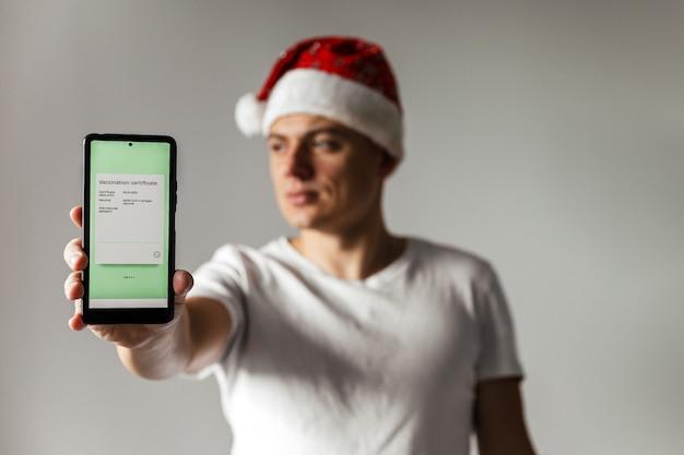 Jonge man met kerstmuts houdt smartphone vast met elektronisch covid-vaccinatiecertificaat