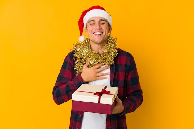 Jonge man met kerstmuts met een cadeau geïsoleerd op gele muur lacht hardop hand op de borst te houden