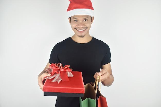 Jonge man met kerstmuts met rode geschenkdoos en boodschappentas