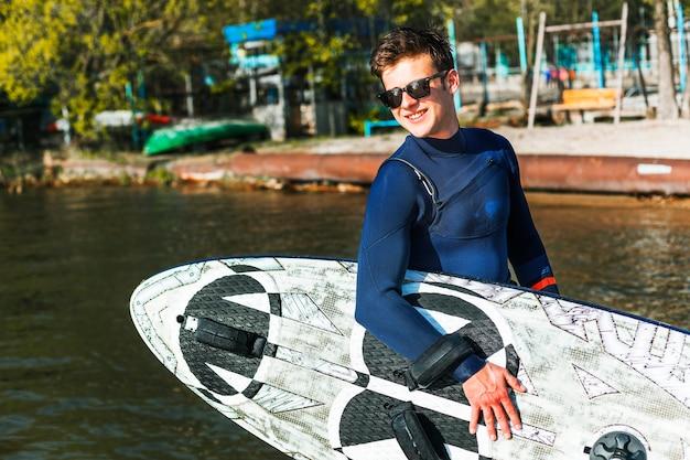 Jonge man met kitesurf bord