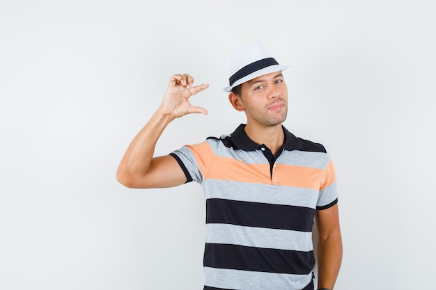 Jonge man met klein formaat bord in t-shirt en hoed en ziet er schattig uit