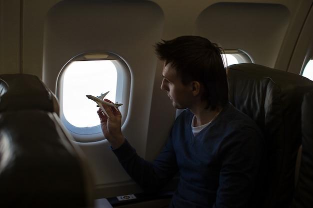 Jonge man met klein modelvliegtuig binnen een groot vliegtuig