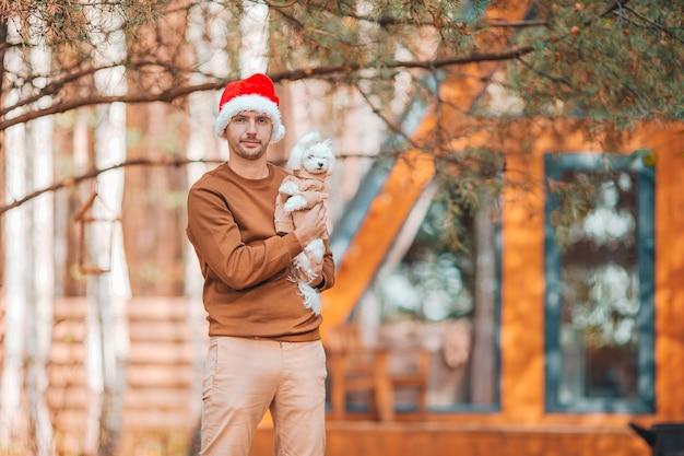 Jonge man met kleine hond op de achtergrond van de kerstmuts van huis