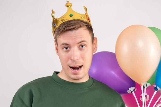 Jonge man met kleurrijke ballonnen op wit