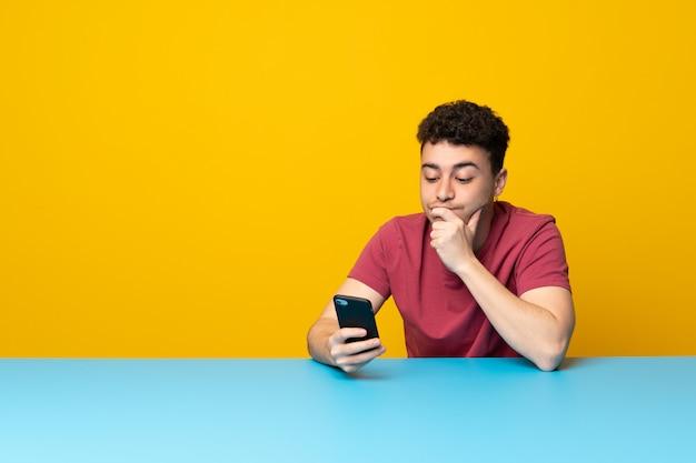 Jonge man met kleurrijke muur en tafel denken en het verzenden van een bericht