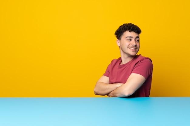 Jonge man met kleurrijke muur en tafel met gekruiste en gelukkige armen