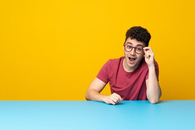 Jonge man met kleurrijke muur en tafel met glazen en verrast