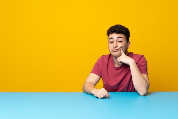 Jonge man met kleurrijke muur en tafel op zoek naar voren
