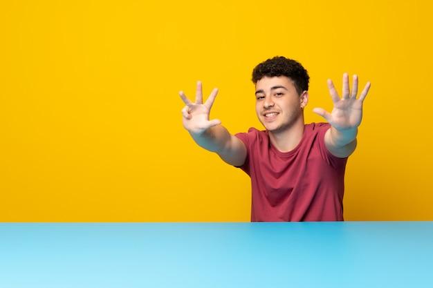 Jonge man met kleurrijke muur en tafel tellen negen met vingers