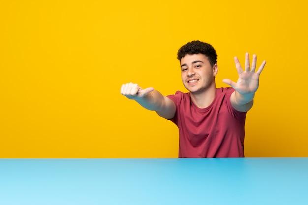 Jonge man met kleurrijke muur en tafel tellen zes met vingers