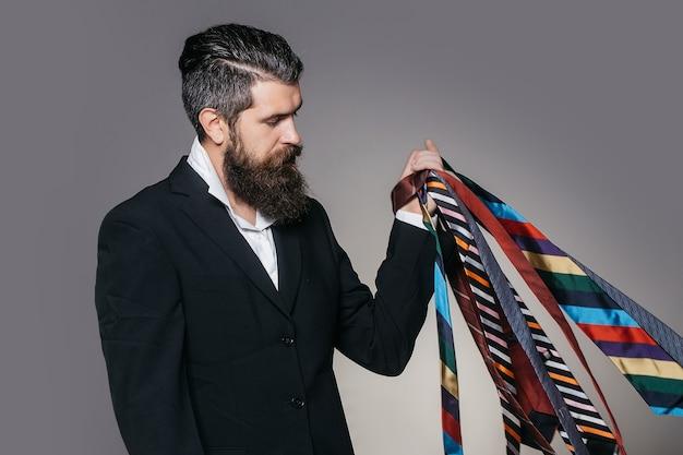 Jonge man met knap ernstig gezicht en baard met veel verschillende banden in zijn hand op grijze studio