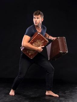 Jonge man met koffers die weglopen. opzij kijken