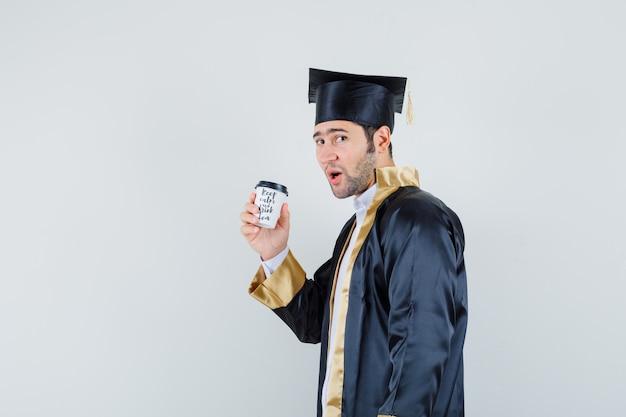 Jonge man met kopje koffie in afgestudeerde uniform en op zoek zelfverzekerd.