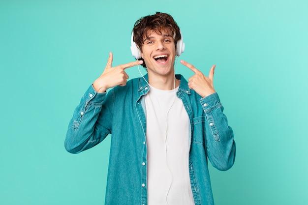 Jonge man met koptelefoon glimlachend vol vertrouwen wijzend naar eigen brede glimlach