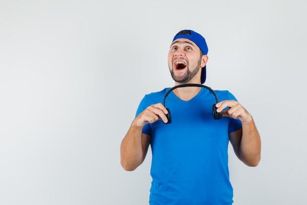 Jonge man met koptelefoon terwijl hij omhoog in blauw t-shirt en pet kijkt en verbaasd kijkt
